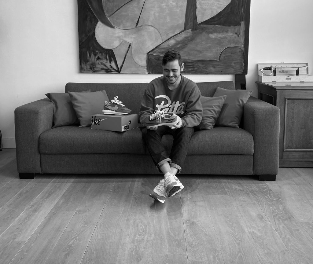 Arthur on the couch holding sneakers
